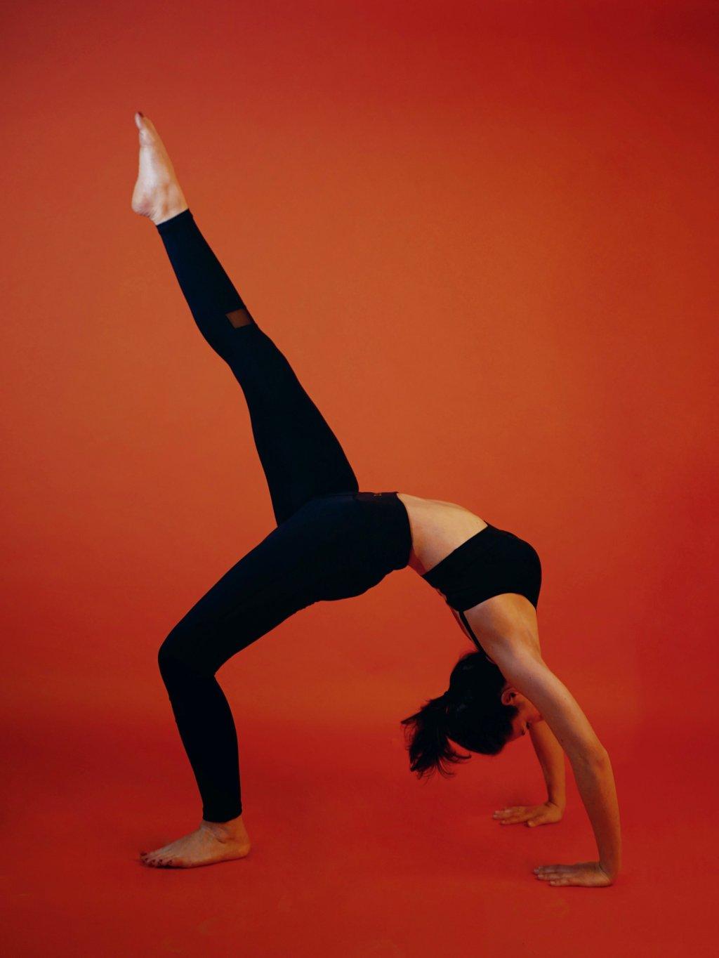 Cette image représente une femme faisant le pont de profil, elle a un pied levé. Elle porte une tenue de sport noir de la marque AZ/AR