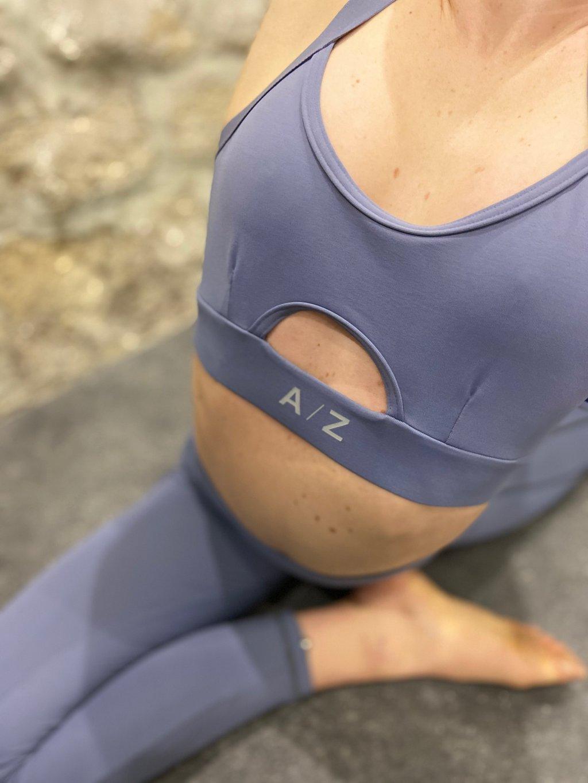 Corps femme assise avec un pied devant elle. On voit son corps du début de la poitrine jusqu'au pieds. Elle porte une tenue de sport de la marque AZ/AR couleur bleu/gris