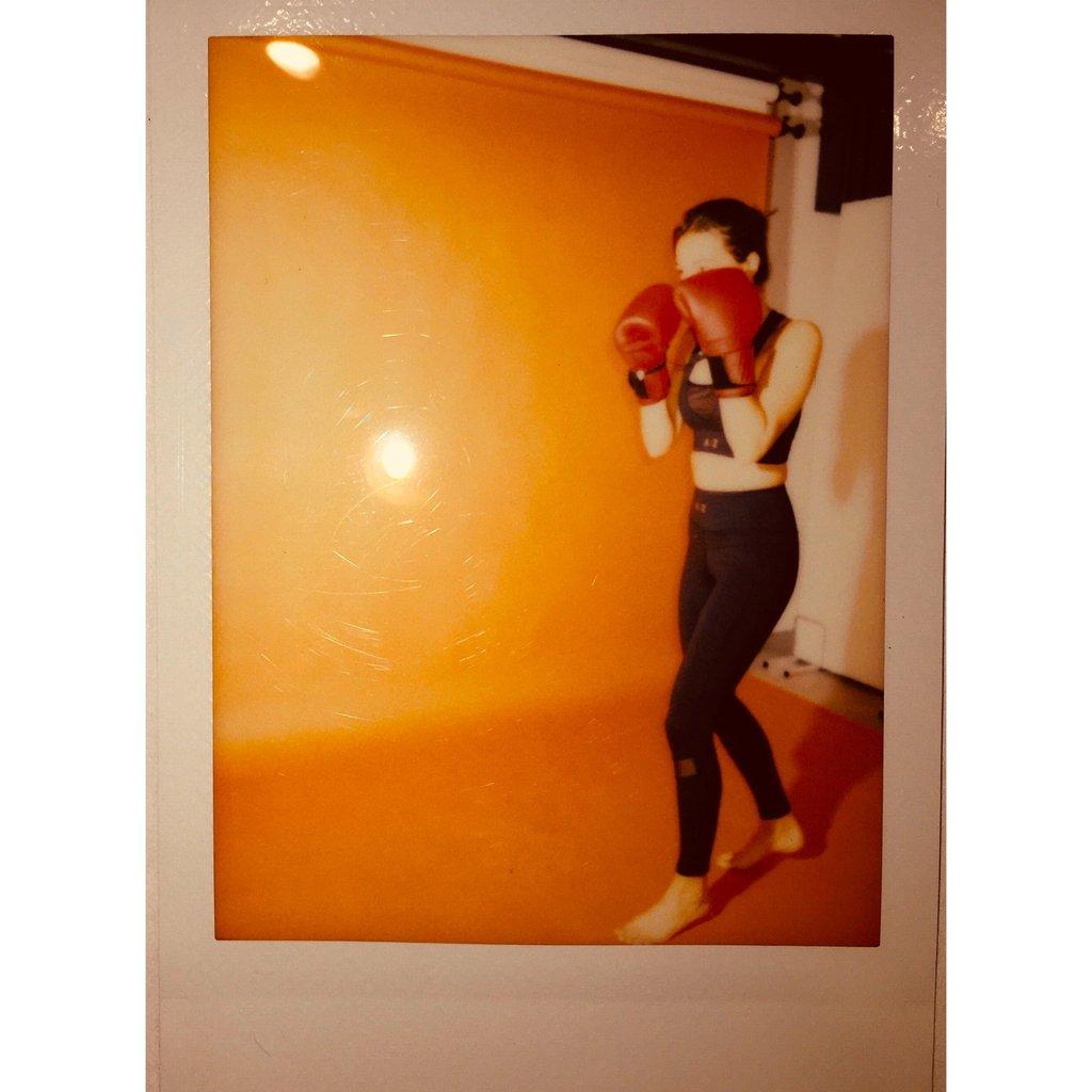 Femme qui porte une tenue de la marque AZ/AR , elle porte des gants de boxe devant elle rouge