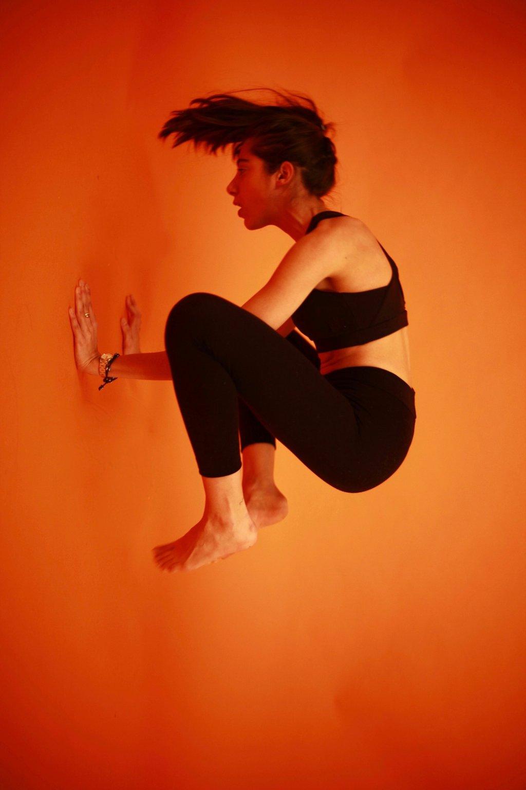 Femme qui fait de l'équilibre sur ses deux mains. Elle porte une tenue de la marque AZ/AR