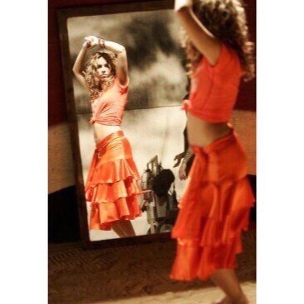 Cette image représente Shakira qui danse devant un miroir