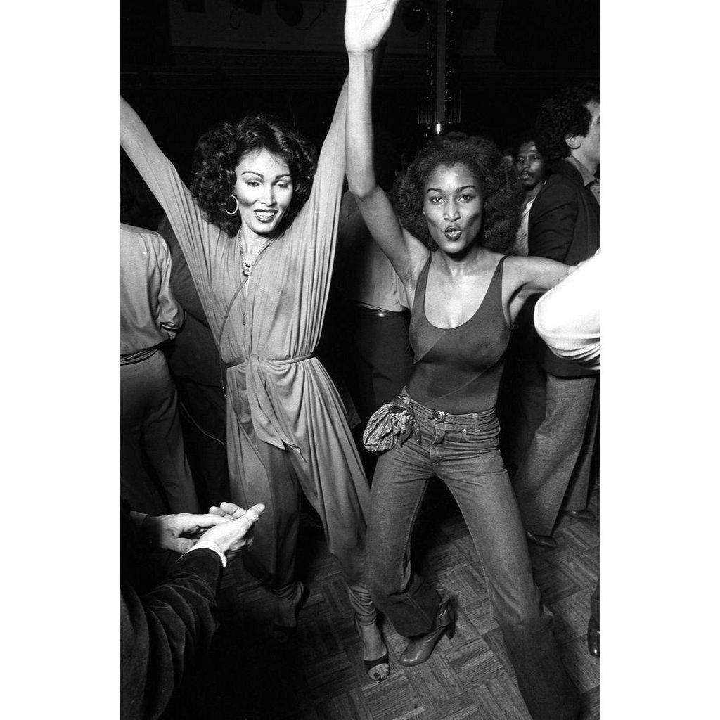Deux femmes dans une discothèque , la photo est en noire et blanc. Elle se tiennent la mains et l'air et sourient