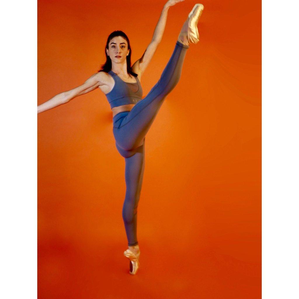 Femme qui porte une tenue de la marque AZ/AR couleur bleu / gris . Elle lève la jambe et porte des chaussons de danse