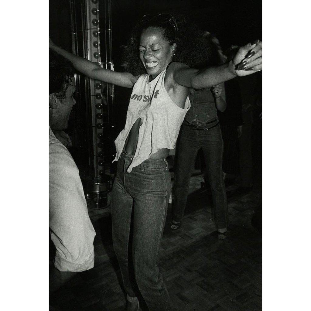 Femme afro qui rigole aux éclats elle a les deux mains levées et l'image est en noir et blanc