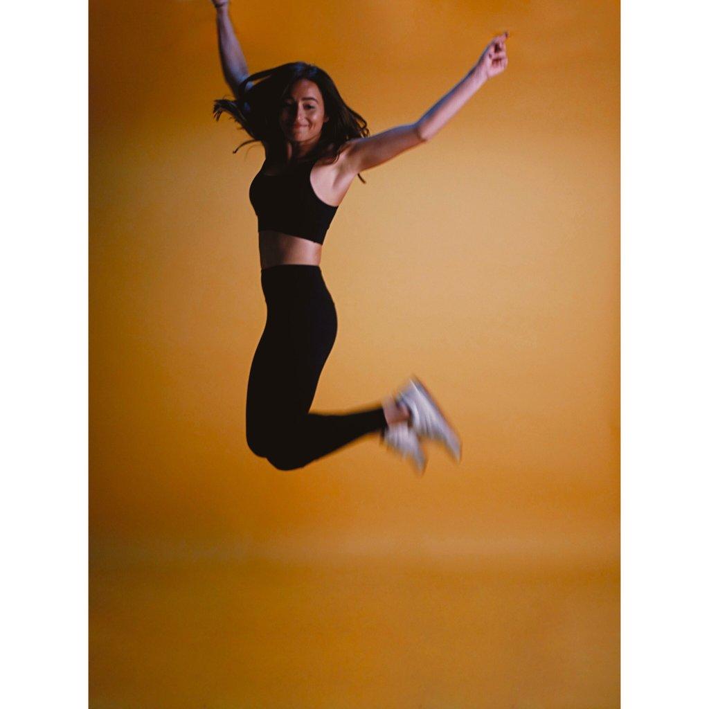 Femme qui porte une tenue de la marque AZ/AR. Elle saute, elle a les mains en l'air . Elle regarde droit devant elle