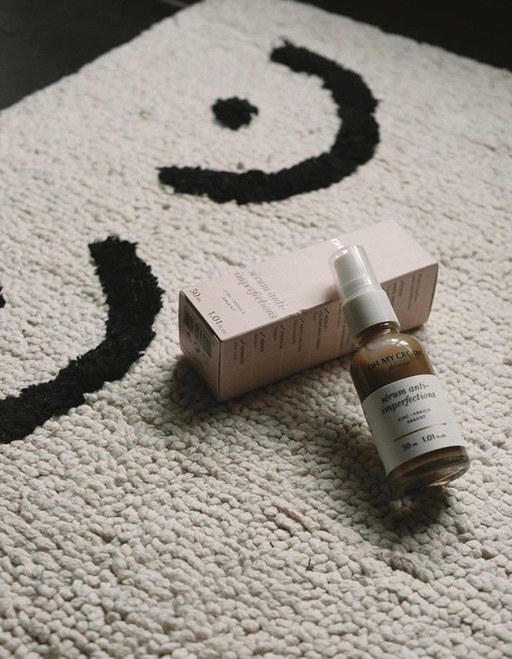 Image représentant un produit cosmétique , le tout est posé sur un tapis qui a un dessin de poitrine  de femme