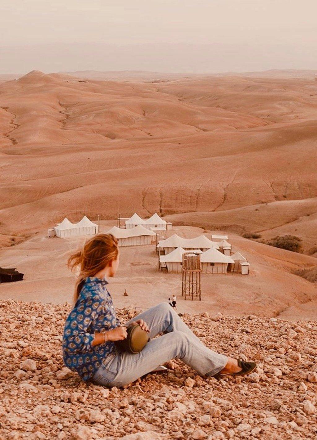 Femme assise dans le dessert regardant devant elle . Elle fait dos à la caméra