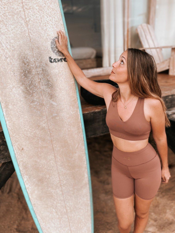 Une femme debout devant une planche de surf, elle porte une tenue Terracotta de AZ/AR , elle a sa main posée sur la planche