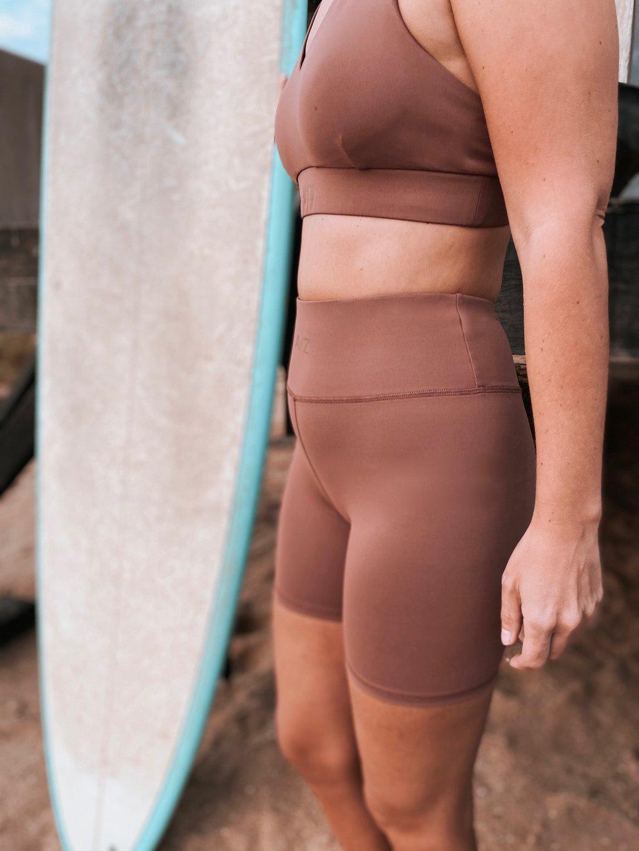 Image représentant un corps de femme du haut de la poitrine au bassin. Elle porte une tenue Terracotta de AZ/AR elle tient une planche de  surf