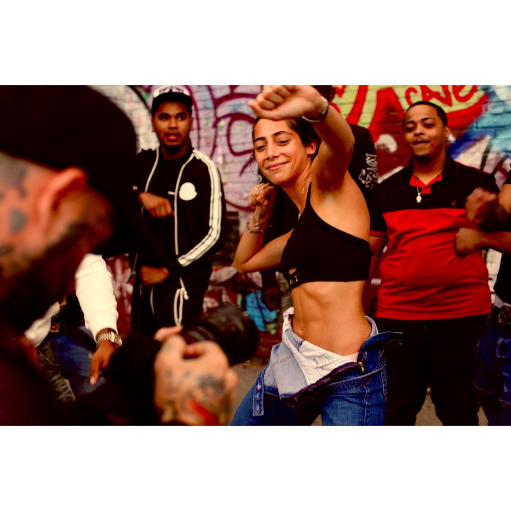 Image d'une femme portant une brassière AZ/AR. Elle danse au milieu d'une foule de personnes
