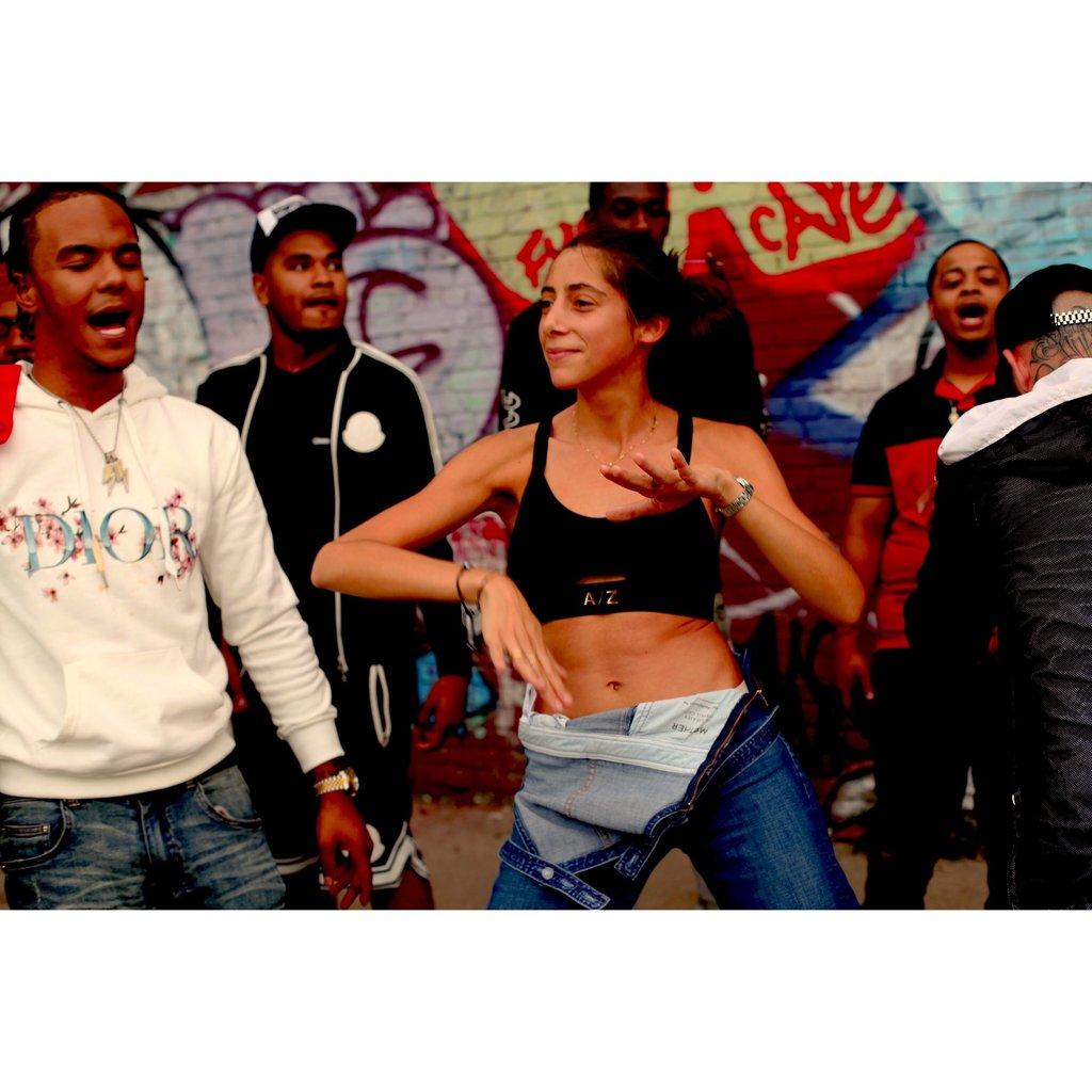 Femme qui porte une brassière de la marque AZ/AR et qui danse dans la rue au milieu d'une foule de personne.