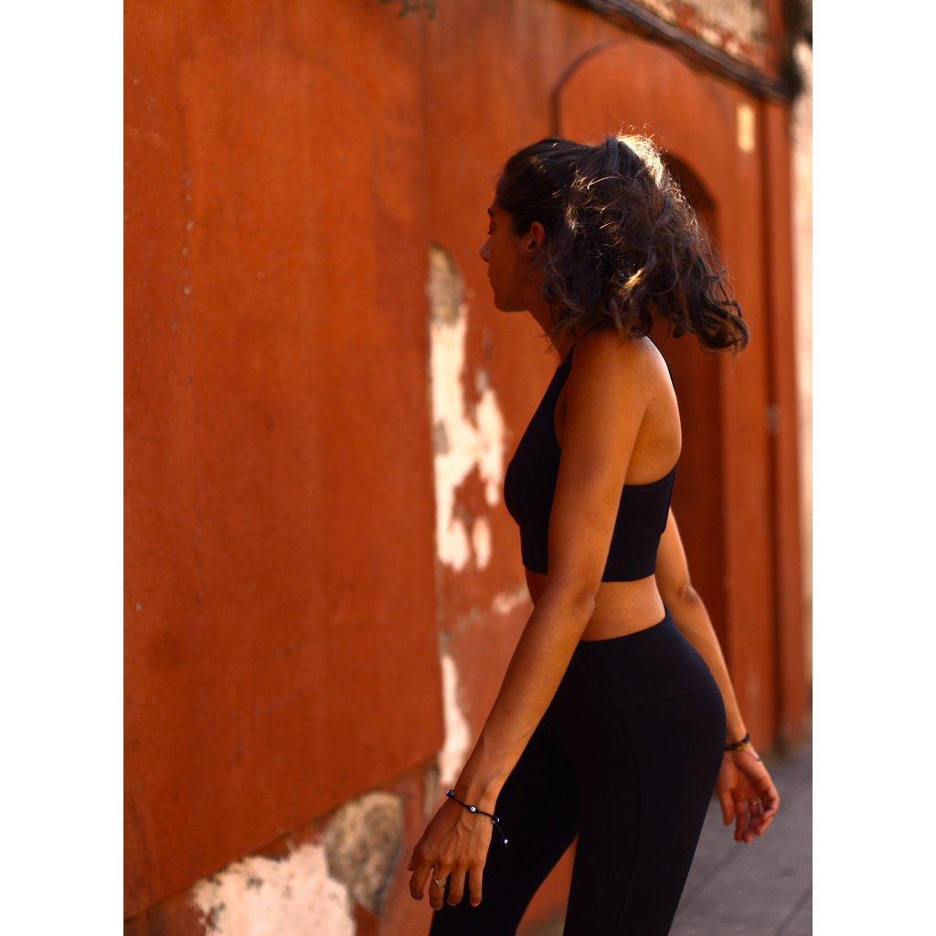 Femme qui regarde derrière elle , elle porte une tenue de sport de la marque AZ/AR noir