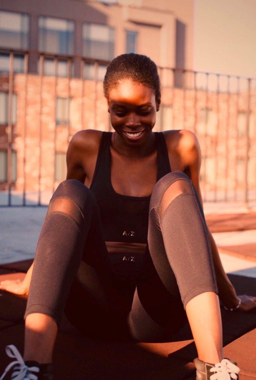 Image femme qui sourit , elle est assise et elle porte un legging noir de la marque AZ/AR