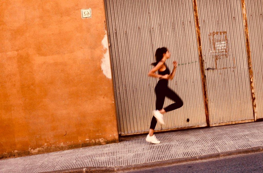 Femme qui court dans la rue, elle porte une tenue AZ/AR noire