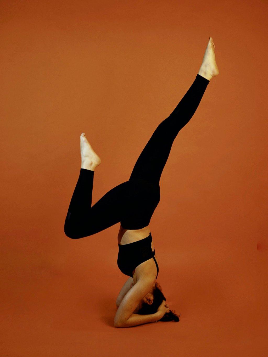 Femme qui porte une tenue de sport de la marque AZ/AR. Elle a les mains sur le sol et les pieds en l'air