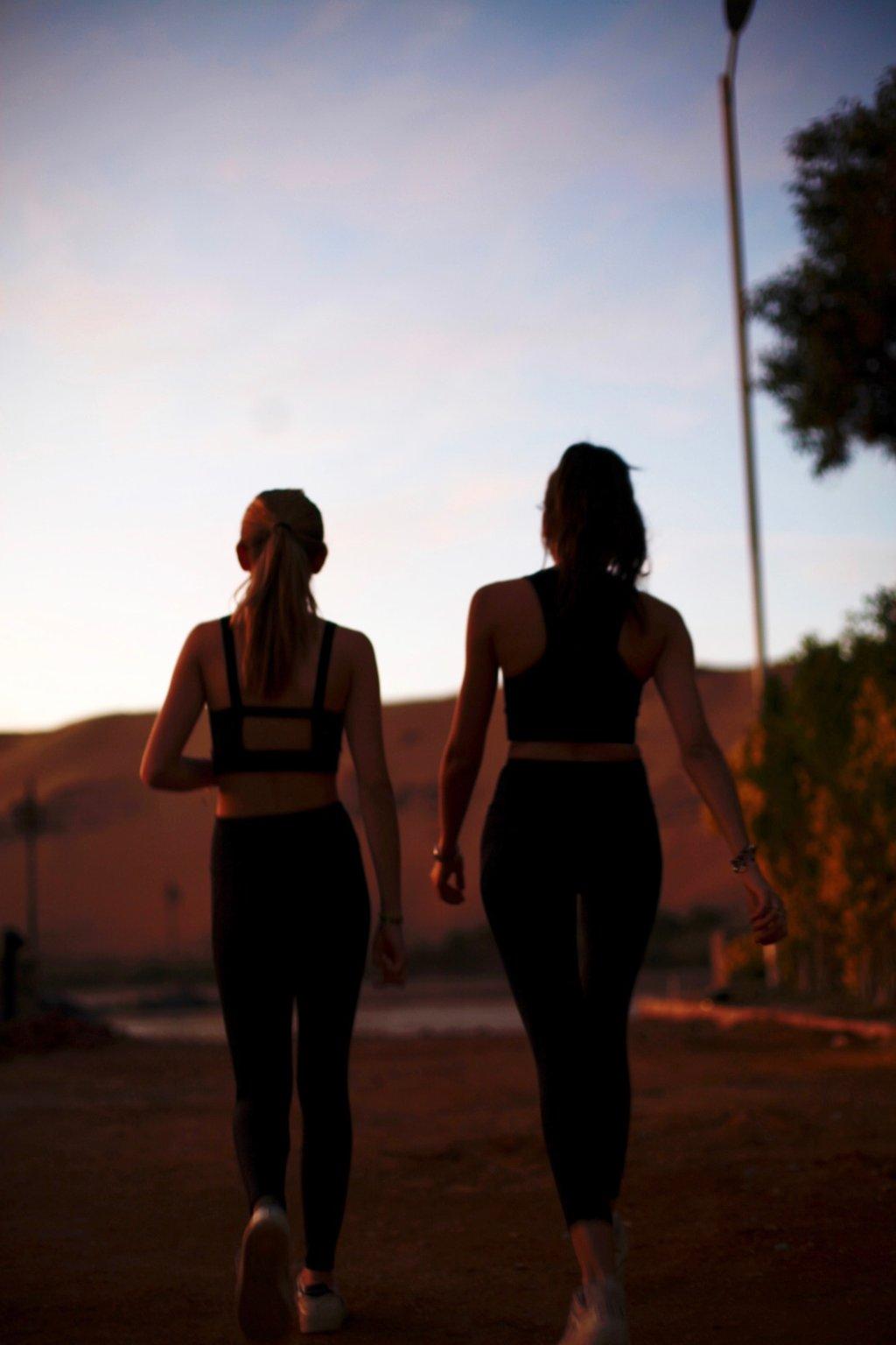 Deux femmes portant des tenues de sport qui marche et qui sont de dos. Elles ont les cheveux attachés