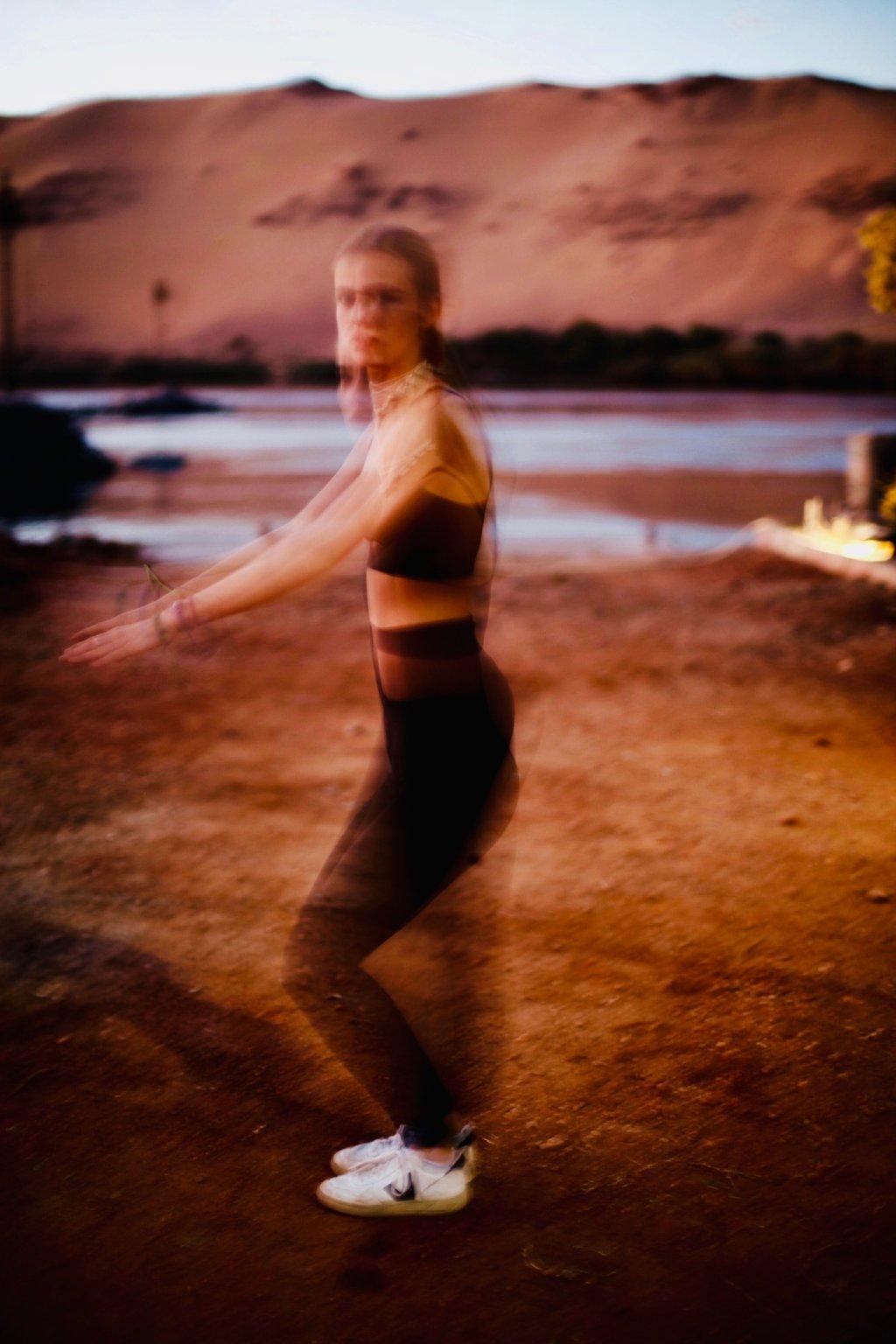 Femme qui fait une traction , l'image est flou , elle porte une tenue de la marque AZ/AR