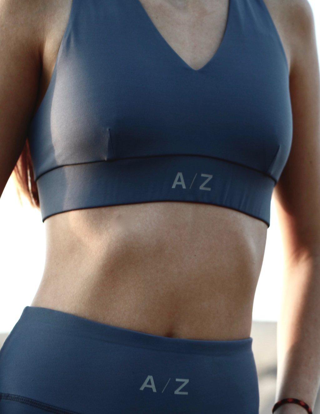 Image femme, on voit son corps du début de la poitrine jusqu'à la taille. Elle porte une brassière de la marque AZ/AR couleur blue/gris