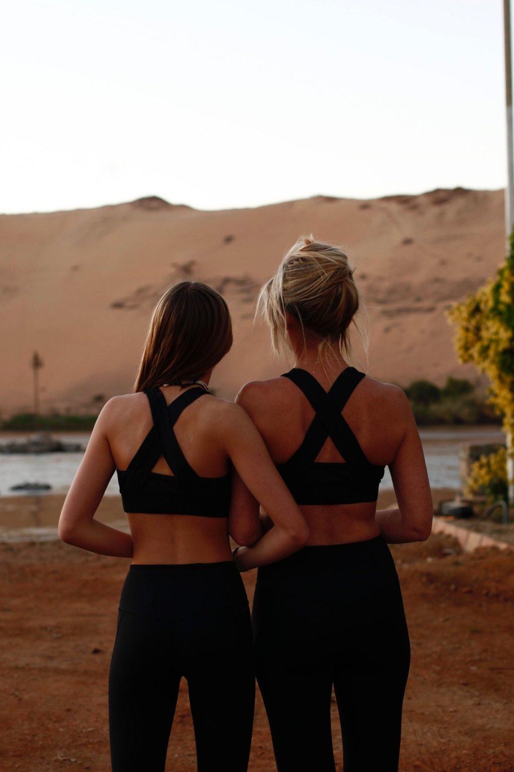 Cette image montre un corps de femme de la poitrine aux jambes. Elle porte une tenue AZ/AR noire et une chemise blanche avec un nœud devant.