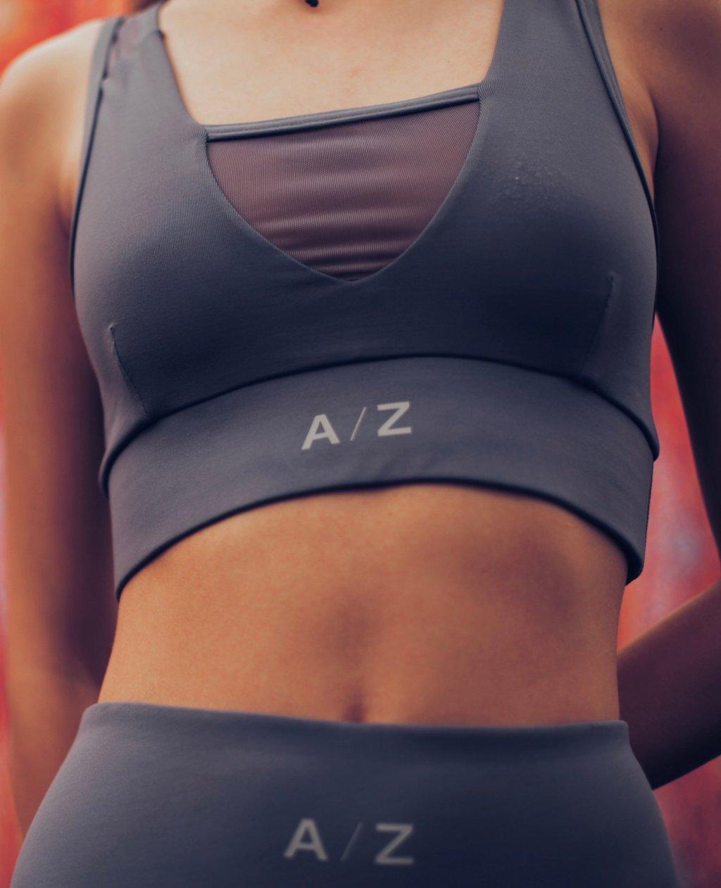 Image femme, on voit son corps du début de la poitrine jusqu'à la taille. Elle a une main derrière le dos. Elle porte une brassière de la marque AZ/AR couleur blue/gris