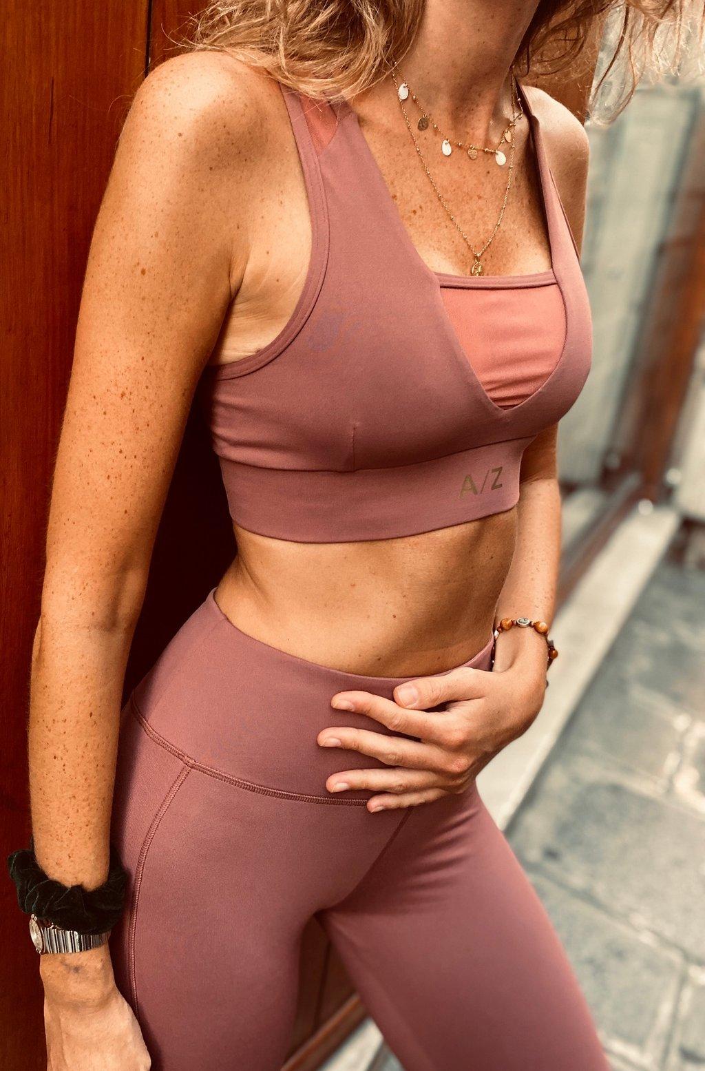 Image femme adossée sur un mur, on voit son corps du début de la poitrine jusqu'aux cuisses. Elle porte une brassière de la marque AZ/AR couleur Terracotta
